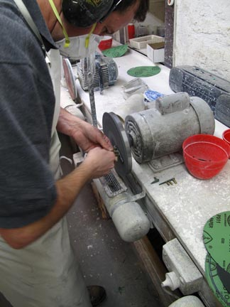 He is Polishing some pendants out of Greenstone (Jade)