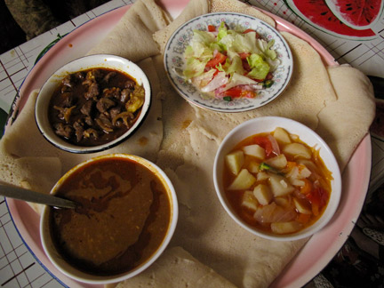 top left: Goat | top right: green salad | bottom right: veggie, potato curry | bottom left: Ethiopian beans.